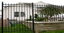 Spear Top Aluminum Fence Panels Used To Create Perimeter Barrier In Conjunction With Landscaping